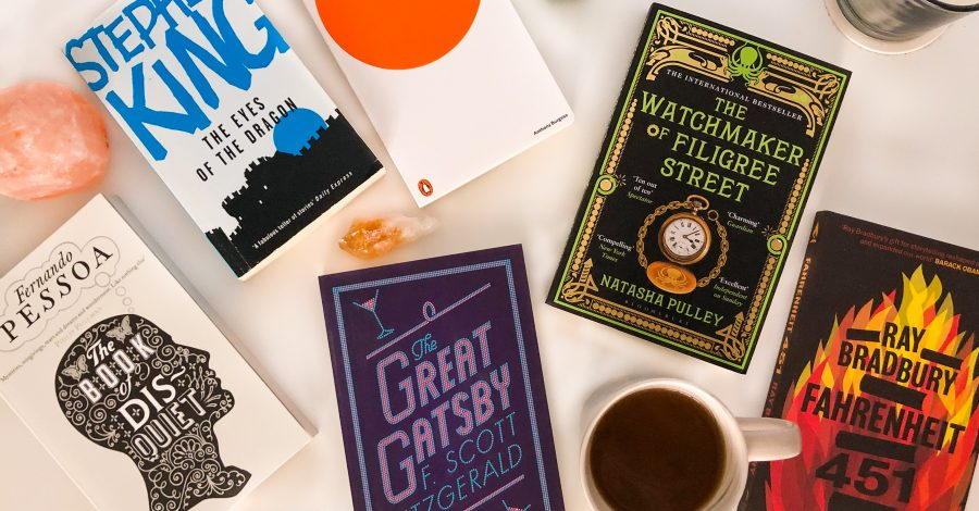 Books on table with candles and coffee for reading in 2020. Help on how to read more books