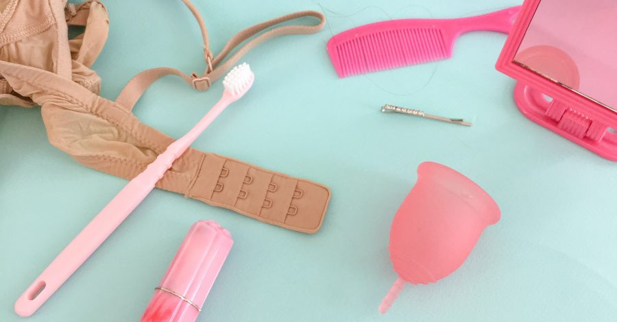 Bra. toothbrush, bag and menstrual cup sit on girl's table for sustainable period care. A beginner's guide to menstrual cups. Lena Cup pictured