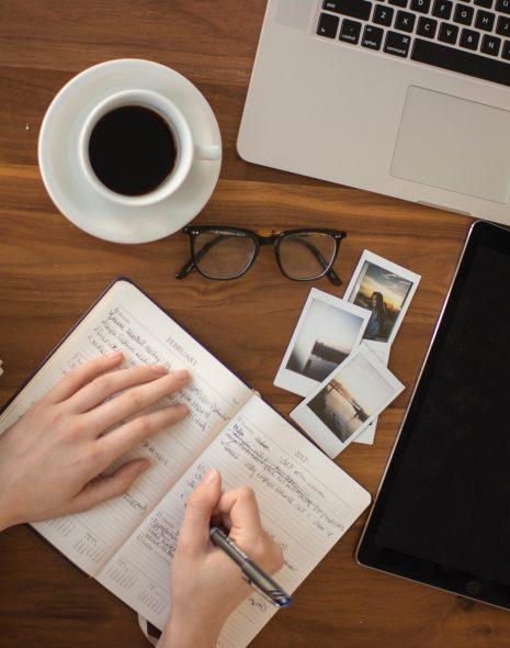 Girl setting achievable goals you'll stick to in notepad with laptop, coffee, photographs and glasses on desk
