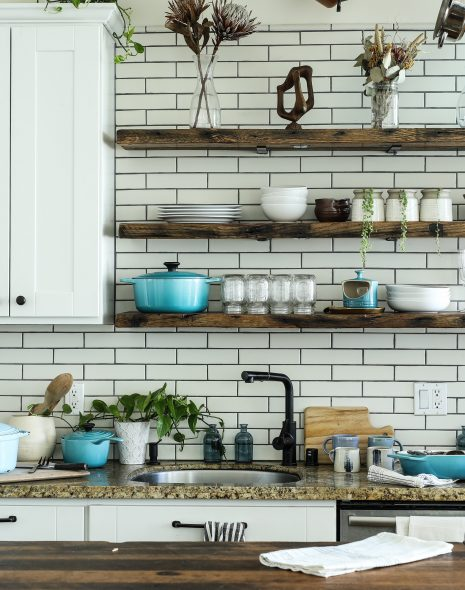 Eco-friendly kitchen products in nice modern kitchen with appliances, cutlery, plates, bowls, sink, shelves, oven, hob, cupboards and green sustainability