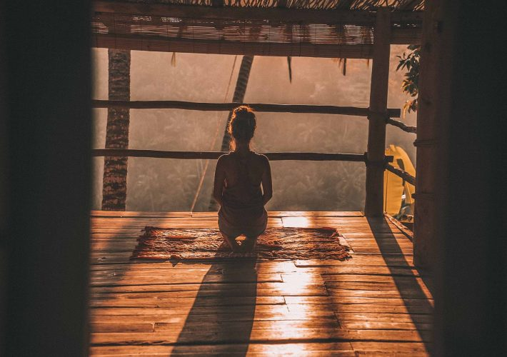 Girl sits and meditates in hut in the sun for wellness in alternative meditation