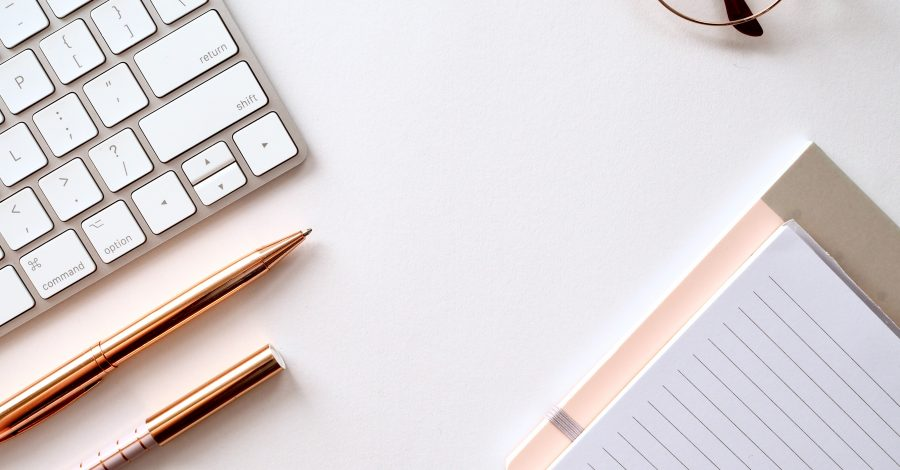 Work, keyboard, glasses, pens and a notebook lie on a desk. How to concentrate with top tips