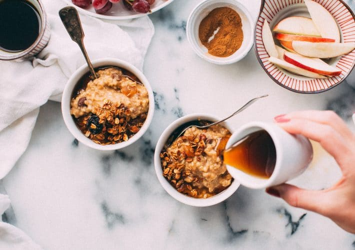 How to create a productive, healthy morning routine - breakfast, granola and oats and porridge and maple syrup with fruit in bowls with spoons on marble table for breakfast in the morning