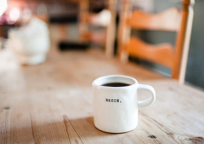 How to wake up early: become a morning person. Coffee cup saying 'begin' lies on wooden dining room table with morning light coming through the window in the early morning.