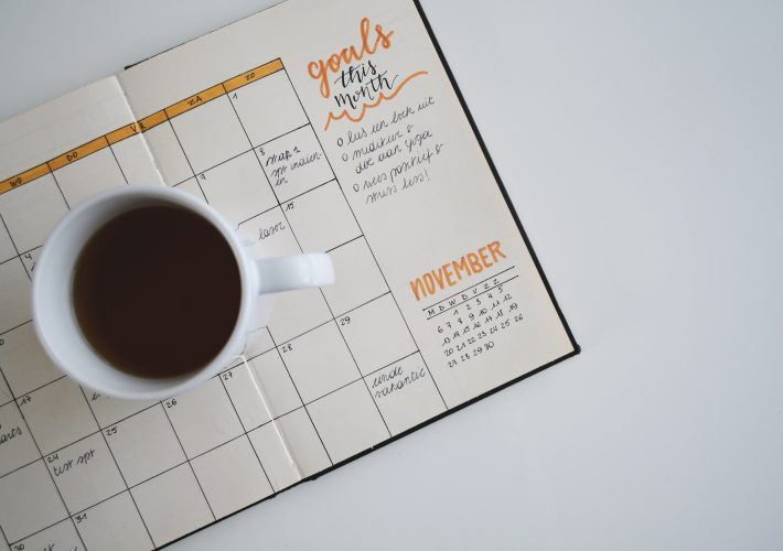 How to stick to goals: my nine strategies for success: mug sits on bullet journal to plan out weekly spread and set and stick to goals