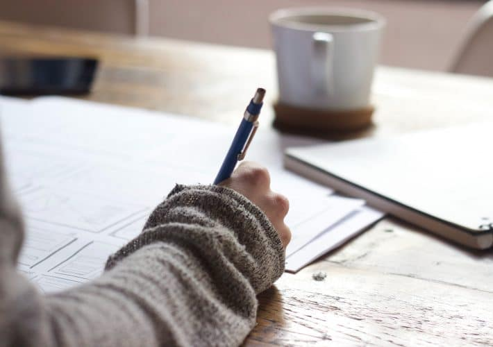 My ultimate guide for finding new hobbies: girl writes in journal on notepad with paper and pen on a desk in the morning with a cup of coffee as her writing hobby