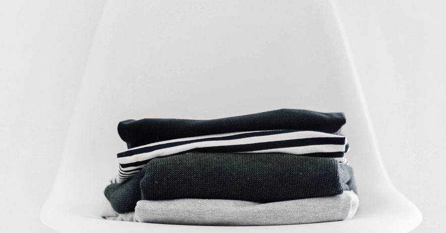 How To Declutter Your Home: A 30 Day Declutter Challenge - piles of clothes lie on chair after being decluttered
