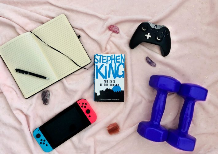 The Ultimate List: 150 Hobby Ideas For You To Try: Nintendo Switch, weights, notebook, Xbox controller, book and stones lay on pink background