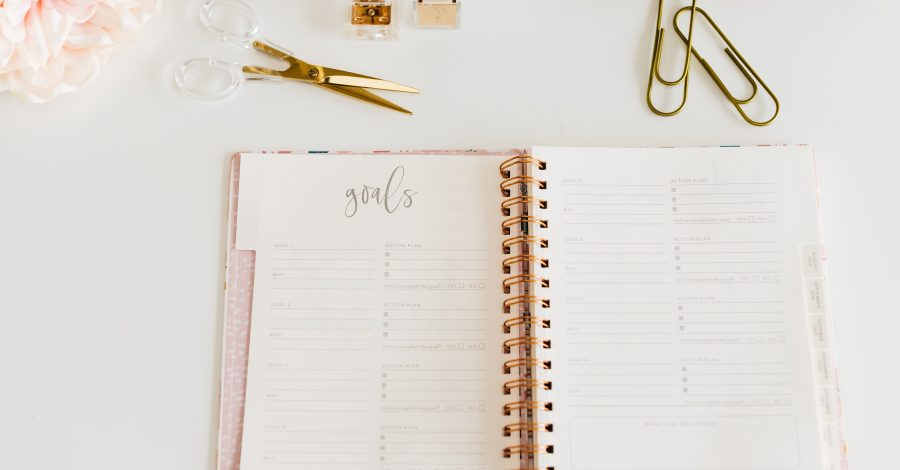 pink agenda, diary journal lie on white desk with gold stationary for planning how to start a routine