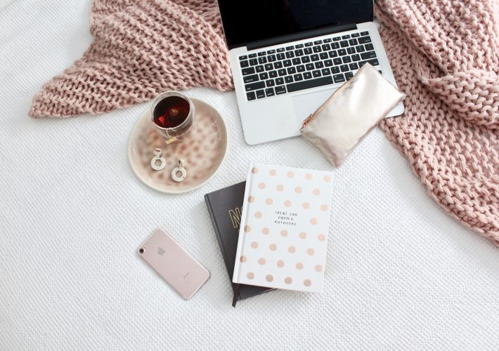 Apple macbook laptop on pink blanket with coffee cup, notepads, pencil case and Apple iPhone on floor. Ready to learn what is the law of attraction and how to use it?