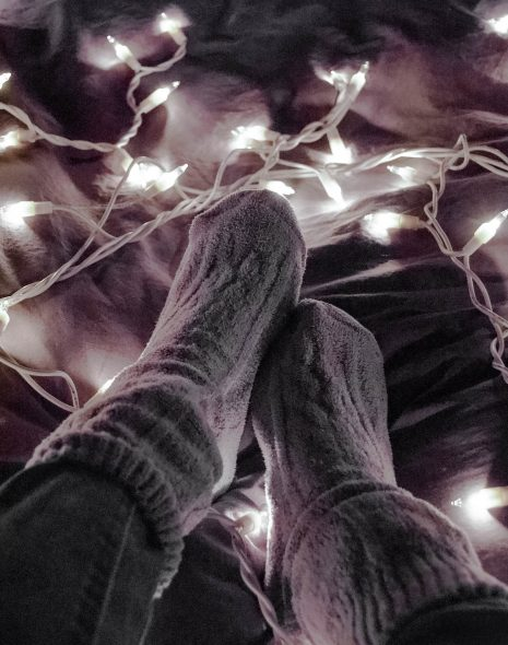 Set daily intentions - cosy socks and dark jeans sit on bed with string lights in a nighttime aesthetic whilst setting a daily intention for goal-setting, motivation, self-growth and inspiration