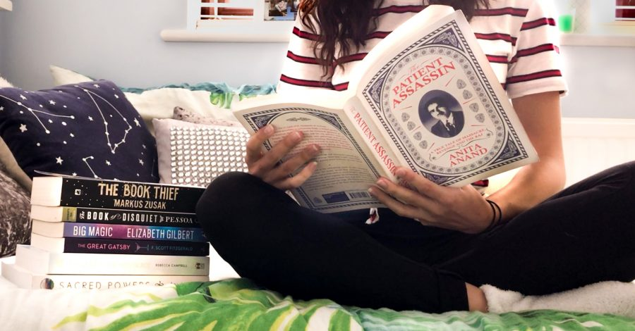 How To Get Started When You Decide 'I Need A New Hobby': girl with brown hair and striped tshirt sits on bed and reads a book with a pile of book and a duvet with a leaf pattern