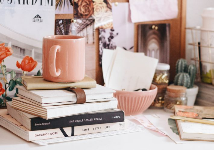 Plan Your Future: How to Create a Life Plan to Build a Future of Success and Happiness - pink mug sits on books and notepads on desk covered with trinkets, notes, plants, photographs and a life plan