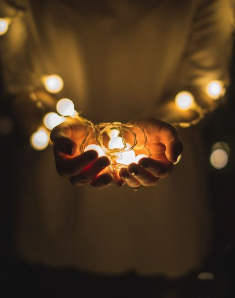 50 Easy Ways To Save Electricity In Your Home - girl holds string lights in hands