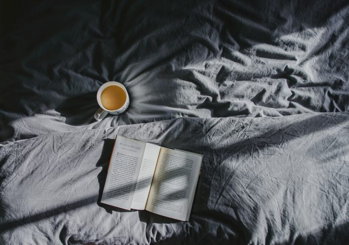 20 wellness inspired morning habits to improve your morning routine - coffee mug and book lie open on grey duvet sheets as sunlight comes across from window in the morning