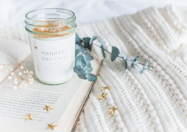 What is manifestation? Manifest and chill mug on a blanket in a cosy room with plants and golden star decorations
