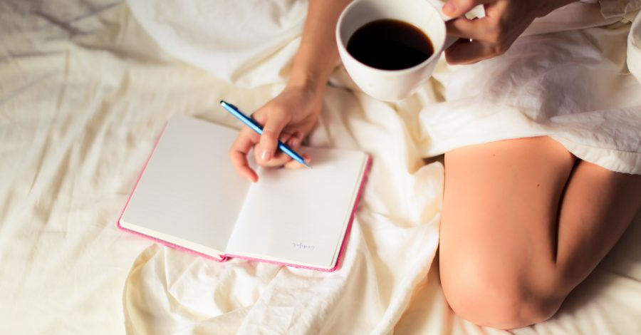 What To Do With Notebooks: 13 Types Of Journal - girl sits on bed with coffee in a mug in her hands and writes in her journal with a blue pen on a white duvet wearing white shorts