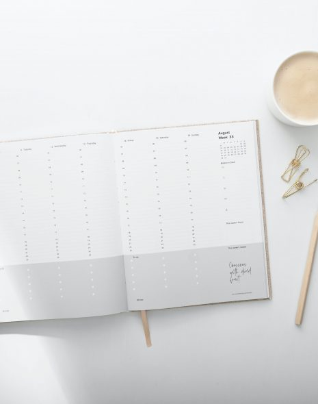 Importance of Routines: coffee cup, gold paper clips, pencil and agenda lie on a table ready to create a new routine and ask what are the benefits of a routine?