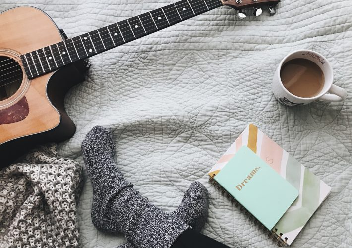 40+ Simple habits to have to change your life - girl in slipper socks and leggings sits on bed with her notepad for dream and habit ideas, next to a coffee, guitar and some cushions.