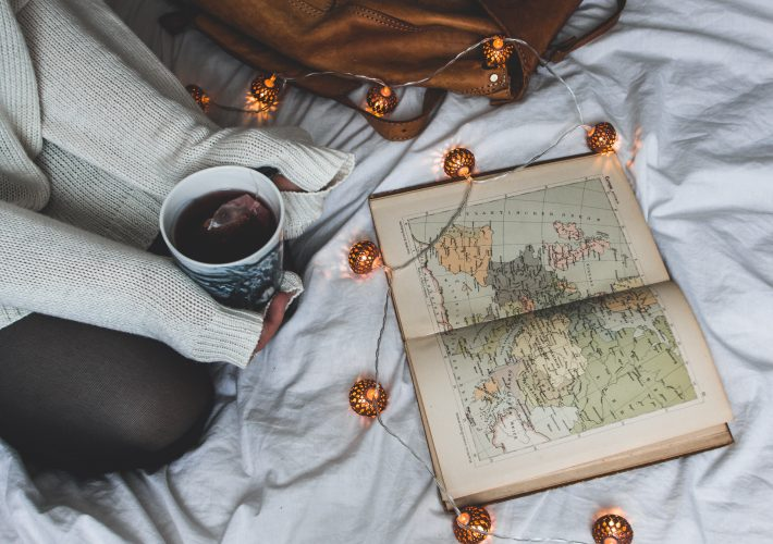 How to achieve your goals: enjoy the journey (the secret of life) - camera, magnifying glass, coffee, pipe, camera, boots, photographs and paper lie on a map of the world with the goal of travelling
