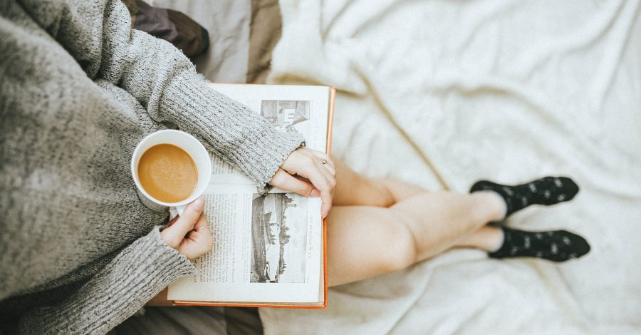 A girl in a grey jumper sits on a bed with a book and a cup of coffee in her lap, with fluffy socks for what to do on a day off on the weekend