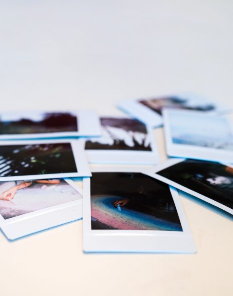 How To Let Go Of Things That No Longer Fit You - Polaroids lie on a table after a break-up or loss in all different colours taken with a Polaroid camera