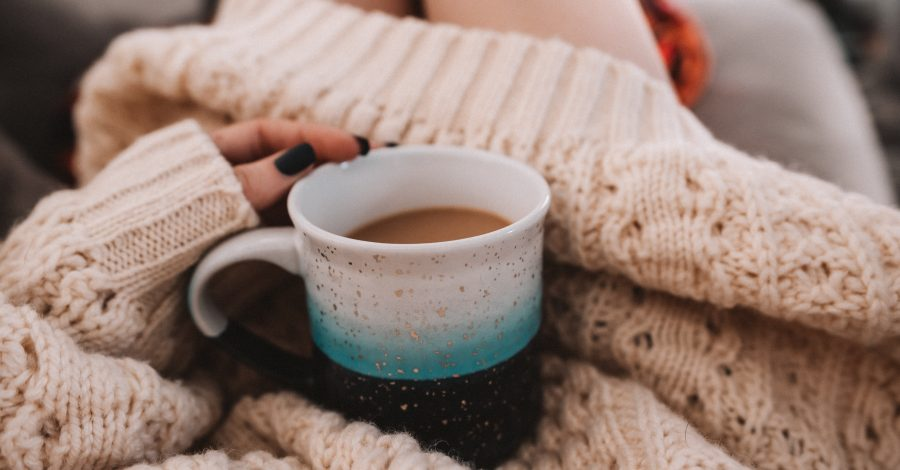 Simplify Your Life: 11 Steps to Intentional Living - girl holds mug of coffee on her lap in oversized wool knitted jumper in the morning