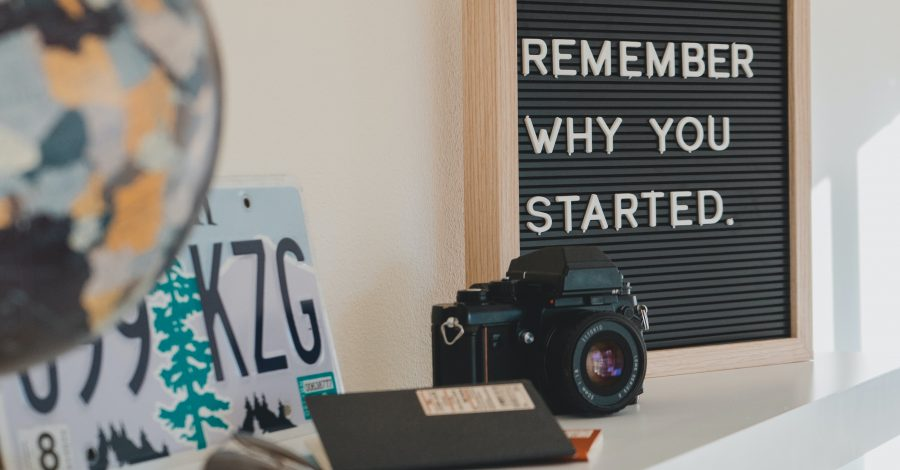 How to Get Motivated: A Guide to Shaking Things Up - board saying 'Remember why you started' sits on desk with camera, book, glasses, map and decorations for motivation and inspitration.