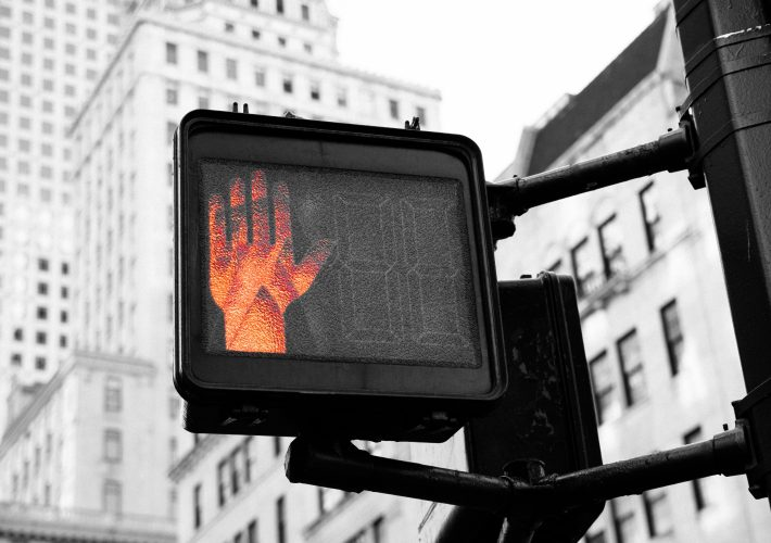 How to Say No: A Guide to Being Nice AND Standing Your Ground - stop hand glows red on stop sign telling people to walk in a city and saying no