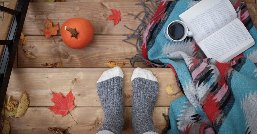 My Cosy Autumn Bucket List 2020 - grey reading socks sat on stairs surrounded by a pumpkin, book, coffee, autumn leaves, and blanket to create an autumn vibe and enjoy the autumn season