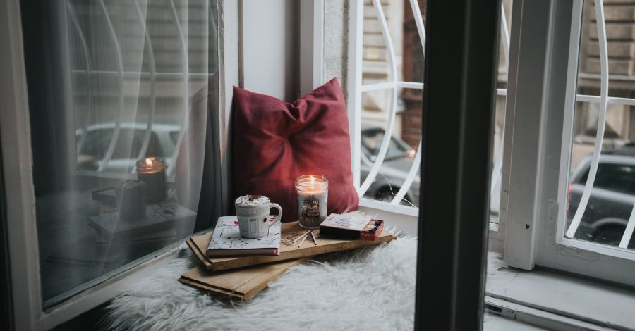 What's the Importance of Faith? It's Not What You Believe In That Matters, Just That You Do - red pillow, candle, book, coffee mug sit on windowsill looking out of window.