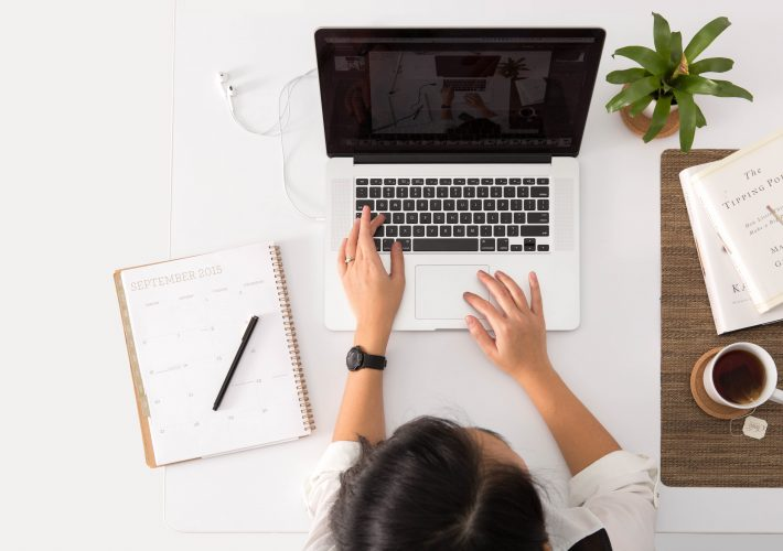 How to Avoid Burnout: 7 Ways to Manage Stress - brunette on laptop with plants and notebook, coffee and notes working on table doing job and managing work life balance