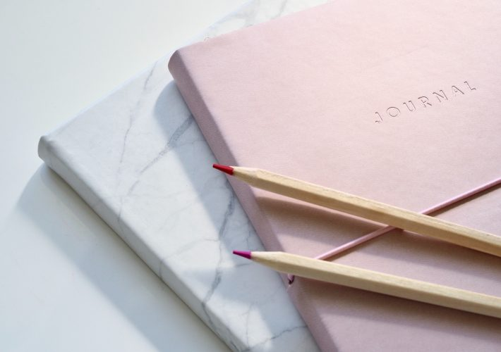 Finding Your Purpose: 8 Journal Prompts to Find Direction - pink and marble journal notebooks lie on white table with pencils ready to journal about life and thoughts on life purpose