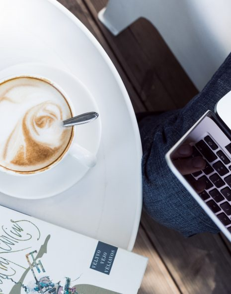 How to Have a Good Day: 9 Simple Tricks - coffee cup sits on table with book and iphone phone next to person typing on laptop on lap outside enjoying good day