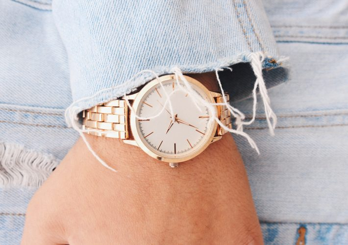 gold metal watch on wrist of girl in denim jacket How to Slow Down Time: Simple Mindsets to Enjoy the Moment
