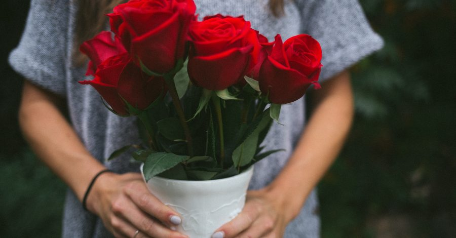 5 Mindsets to Practice Compassion and Boost Your Happiness - woman with brown hair in grey big tshirt hands flower pot of red roses as a gift to practice compassion