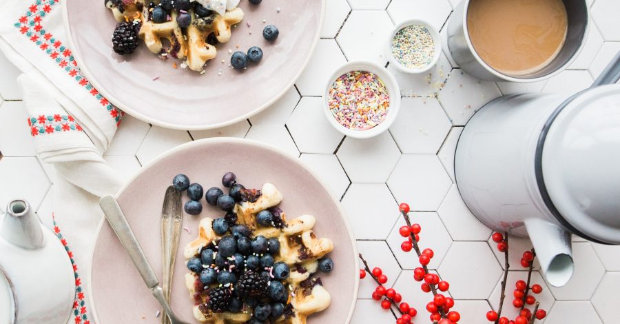 How to Become Vegan: My Story + How to Get Started - vegan waffles with blueberries, seeds on pink plates next to a coffee pot and coffee in a mug for a vegan breakfast