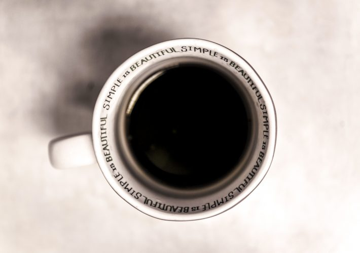 How to Achieve an Abundance Mentality: The Four Principles of Happiness - coffee cup with black coffee and mug that says 'beautiful simple' around the rim on concrete worktop
