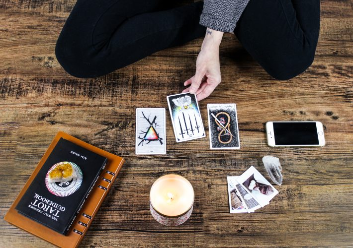 How to Get Started With Tarot: My Journey & The Basics You Need to Know - girl in jumper and black leggings sits on wooden floor pulling Wild Unknown by Kim Krans tarot cards, with crystals, a candle and an iphone.