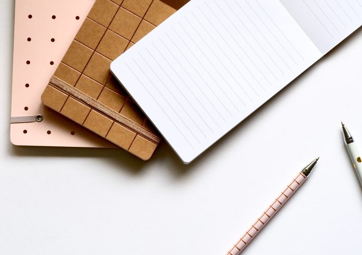 6 Simple Tricks to Help Improve Focus - white, brown and pink notebooks lie on a table desk next to some pens as stationary used for a work day, career and studying