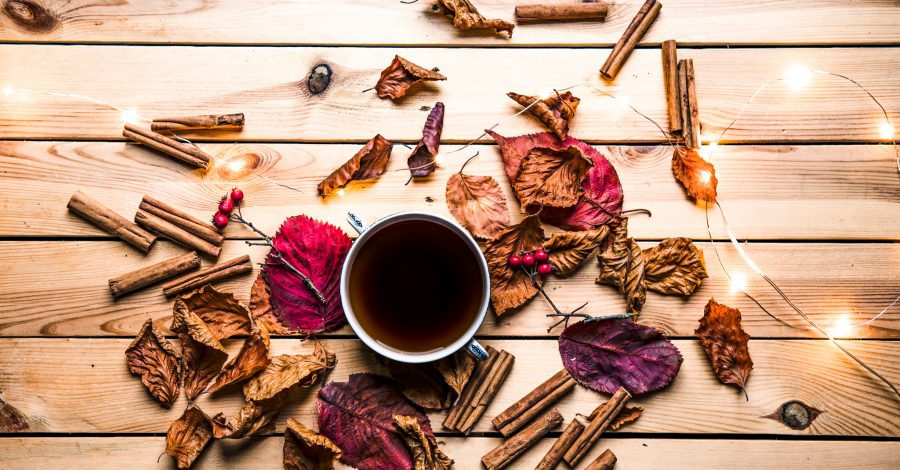 7 Reasons to Love Autumn This Year. Cinnamon sticks, leaves, fairy lights and a mug of coffee sits on wooden flooring in autumn