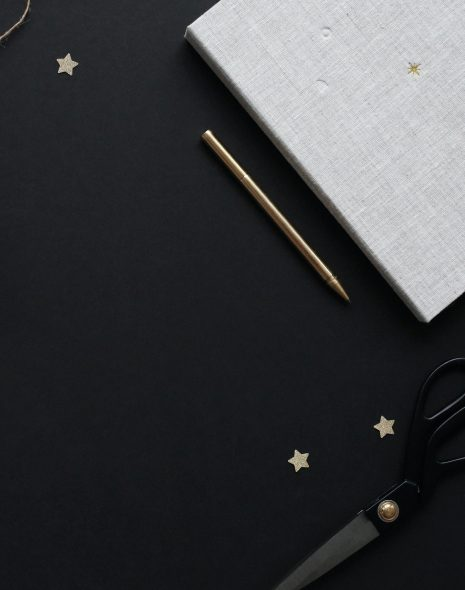 How To Plan Your Day: 10 Steps to Your Perfect Daily Routine. Notebook, scissors, crafts and pencil on a desk with little gold stars