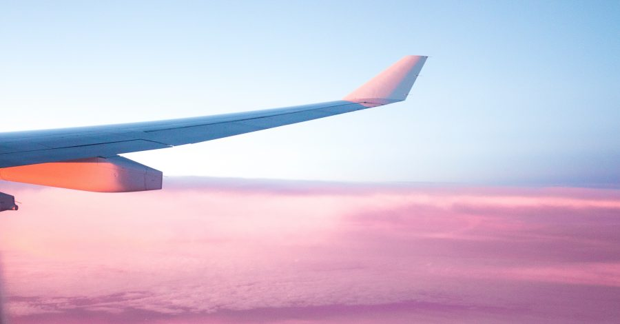 How To Plan a Trip: Your Holiday Checklist. View of a plane wing out of a plane window above pink clouds and a blue sky
