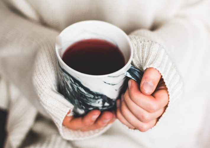 berry tea in mug with long sweater sleeves for ways to boost your morning motivation