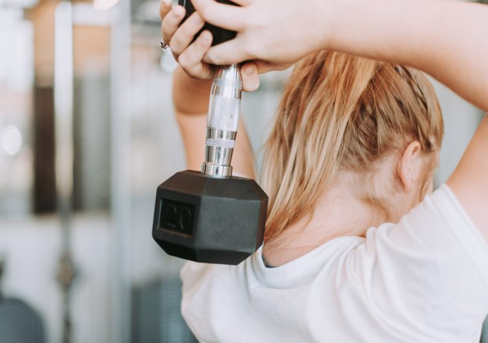 Blonde woman uses weights weightlifting at the gym doing fitness and exercise to become your healthiest self