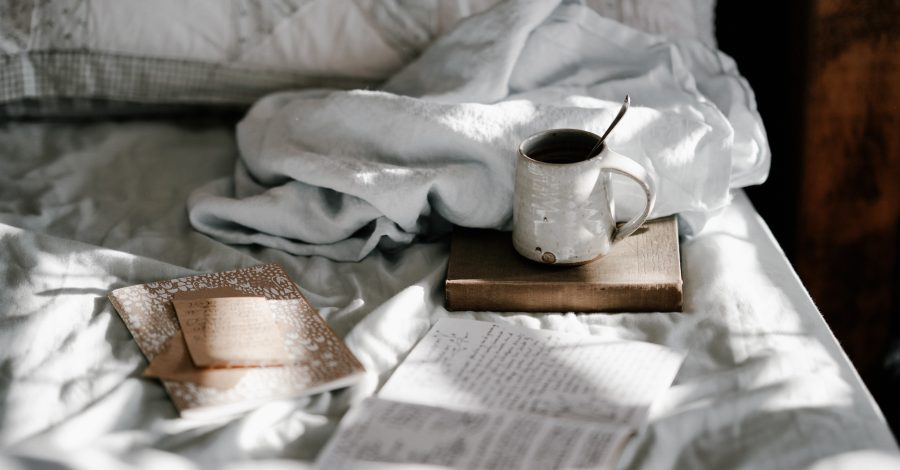 75 Journal Prompts for Self-Discovery written in a journal on bed with coffee and book