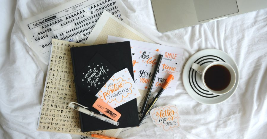Bulet journal, resources, coffee and laptop lay on bed for planning and organisation, but What is Bullet Journaling? The Pros and Cons of Using a Bullet Journal