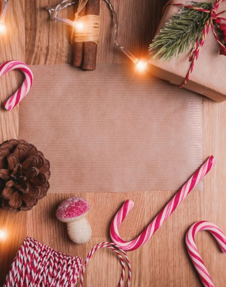 Candy canes, presents wrapped in brown paper with red string, leaves, lights and pinecones with stars laid out as a Christmas flatlay on a wooden table.23 Ways to Celebrate Christmas: My Christmas Bucket List 2020