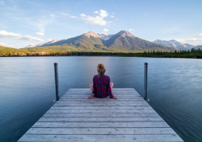 Girl with blonde haired bun sits on the end of a jetty looking out over a blue lake at mountains in the distance. She ponders about how to push yourself out of your comfort zone