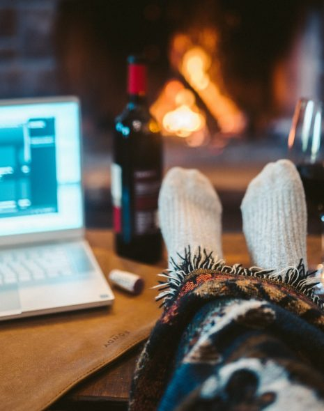 My Christmas Film List: The Best Movies for Christmas - feet up in winter socks in front of the fire with laptop with Christmas films to watch with red wine for Christmas